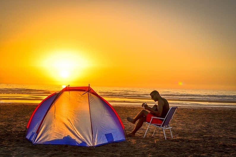 man on with a tent on the beach