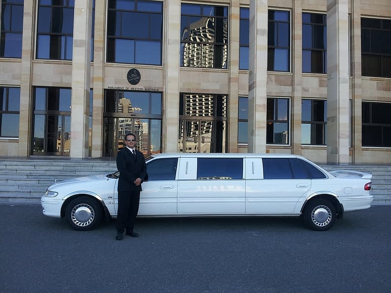 man standing right next to the white limousine